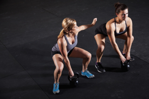 Female athletes working out with kettle bells